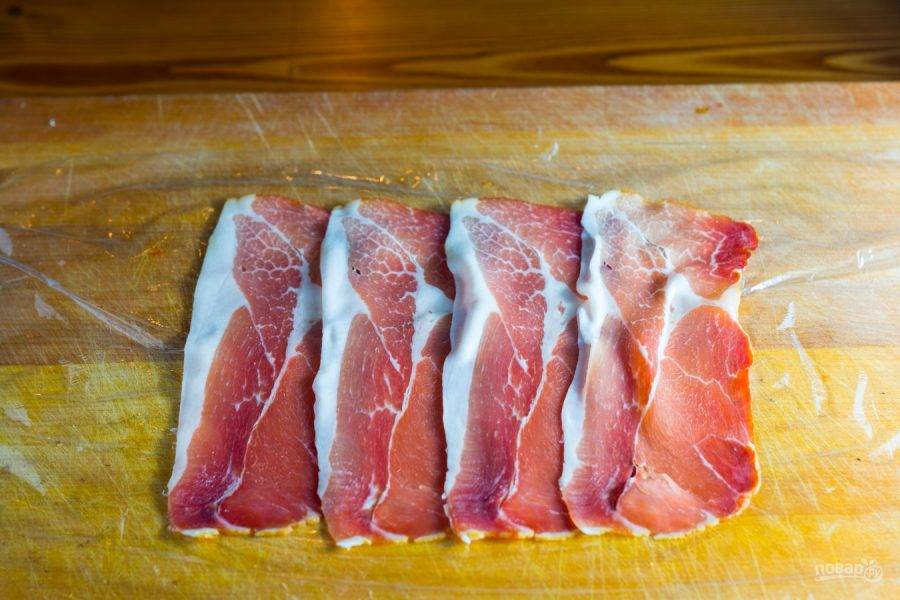 6.Расстелите пищевую пленку, выложите ломтики прошутто внахлест друг на друга.