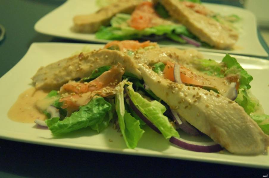 """Куриное филе нарежьте на полоски и обжарьте с двух сторон на растительном масле. Выложите его в тарелку. Туда же отправьте вымытые листья салата """"Ромен"""", лук, зелень и маринованный имбирь. Полейте все заранее приготовленным соусом и посыпьте обжаренным кунжутом."""