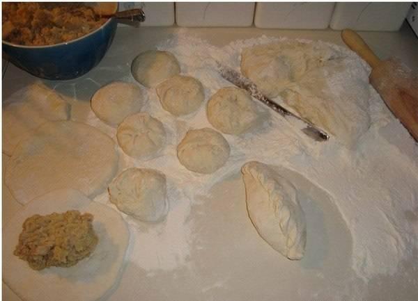 Ножом разделите тесто на кусочки, сформировав из них шарики. Затем раскатайте шарики в пласты, примерно в 1 см шириной. Внутрь вложите начинку и сформируйте пирожки.