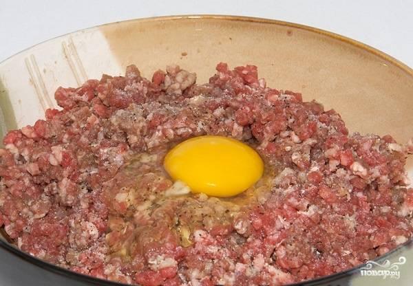 2. Мясо пропустите через мясорубку вместе с луком и чесноком. Вбейте яйцо. Посолите и поперчите по вкусу.