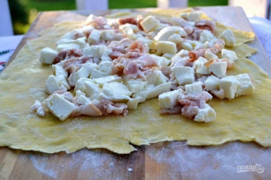 5.Достаньте тесто из холодильника и раскатайте его тонко, по центру выложите бекон с сыром, отступая от края 1-2 см.