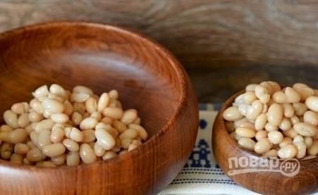 Откройте банку консервированной белой фасоли и слейте с нее лишнюю жидкость. Переложите четыре столовые ложки фасоли в блюдо для подачи.