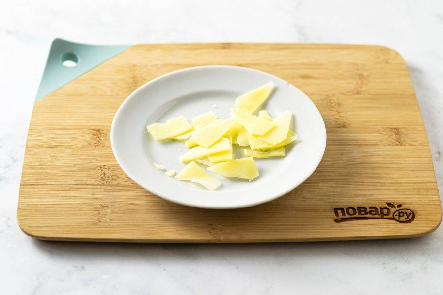 Пармезан нарежьте тонкими ломтиками с помощью овощечистки или ножа для сыра.