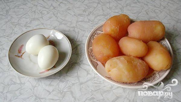 1.Промываем картофель, и приблизительно минут двадцать-двадцать пять отвариваем в подсоленной воде (картофель варим в мундире), после картофель от кожуры очищаем. Вкрутую сварим яйца, остуживаем и очищаем от скорлупы.