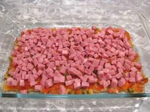 4. Теперь режем ветчину мелким кубиком, часть выкладываем сверху. Должен получится как бы один слой. Наверх - снова листы лазаньи и томатная смесь.