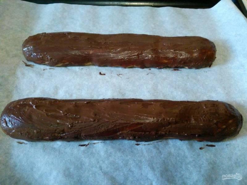 Смешайте какао-порошок с оставшимся желтком и равномерно нанесите получившуюся массу на поверхность сформированных из теста колбасок.