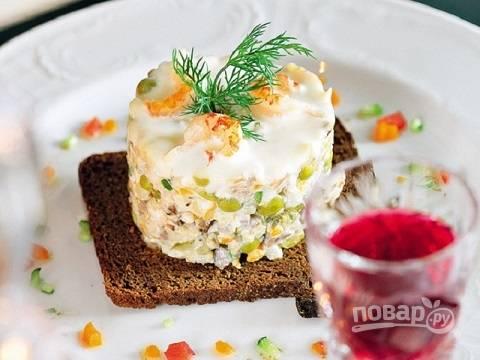 С помощью кулинарного кольца красиво выкладываем салат, украшаем его креветками и зеленью.