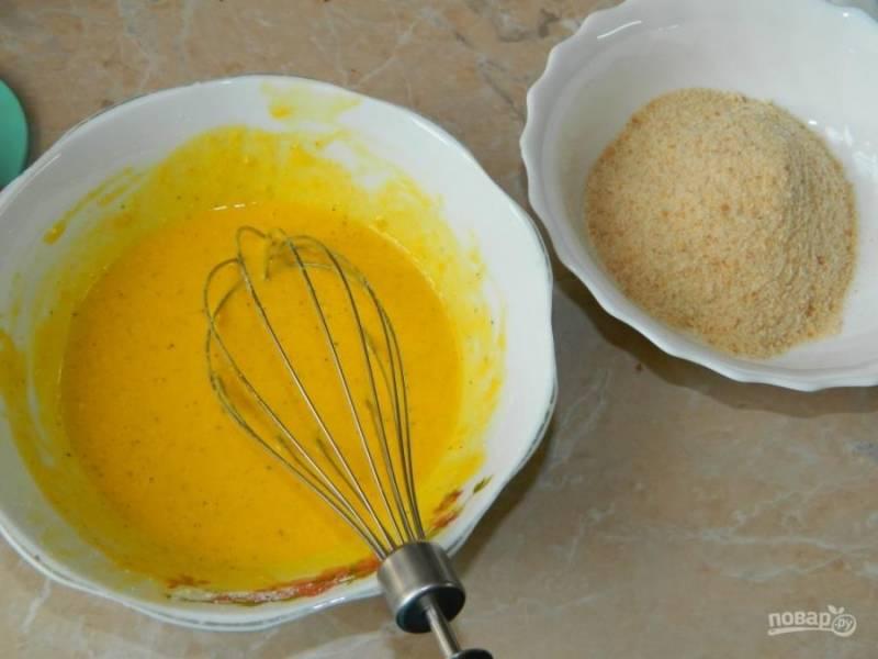 Куриные рулеты обмакните в яичную смесь и панировочные сухари.