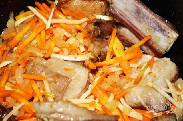 Затем в казан добавьте сельдерей и морковь. Тушите ингредиенты, помешивая, до выпаривания жидкости.