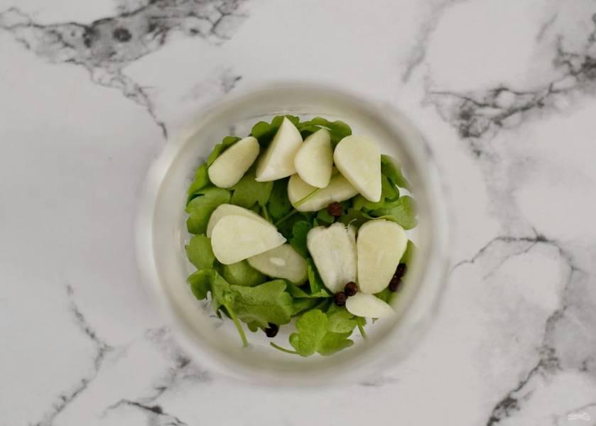 Пока перцы варятся, подготовьте стерилизованные баночки. На дно положите петрушку, нарезанный пластинами чеснок и перец горшком.