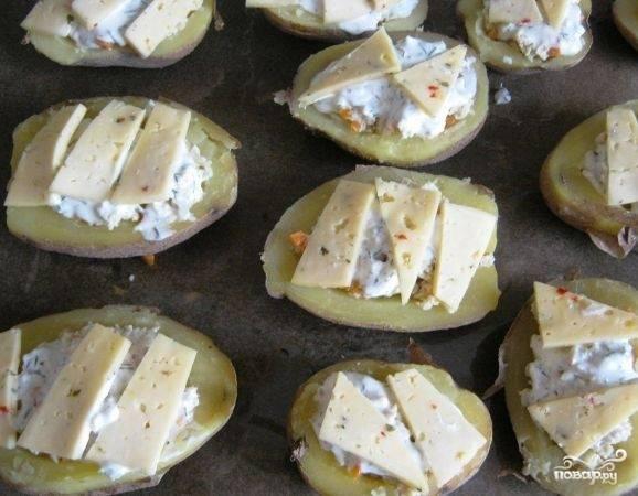 Картофель разрежьте пополам и в середине каждой половинку сформируйте углубления. Столовой ложкой выложите начинку, затем на каждую картошку выложите сметану и пару кусочков сыра.