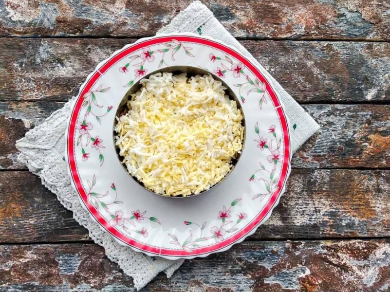 Сверху грибов сделайте слой из натертых на мелкой терке яиц и смажьте их майонезом.