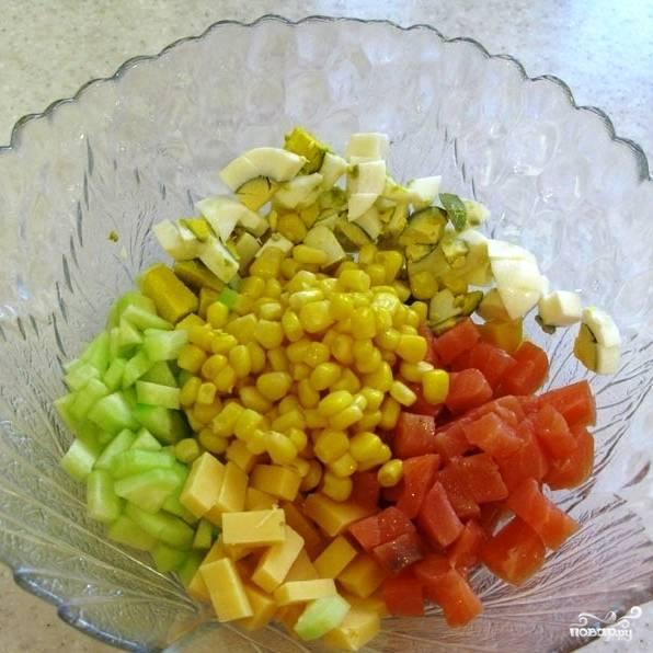 Смешиваем все нарезанные ингредиенты, туда же добавляем консервированную кукурузу (без жидкости).