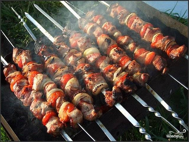 Нанизываем мясо, чередуя его с кольцами лука и помидорами, на шампуры и запекаем на углях до готовности. В процессе сбрызгиваем все тем же вином, разведенным 1:1 с водой.