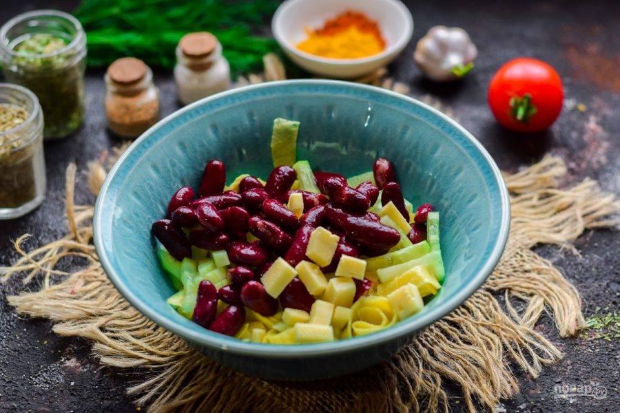 Следом добавьте в салат красную фасоль и немного нарезанного кубиками твердого сыра.