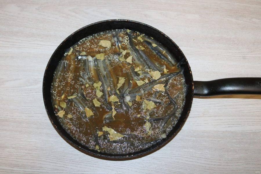 Залейте чаем рыбу. Выдавите сок из лимона, полейте им рыбу. Поставьте на огонь, доведите до кипения, готовьте на медленном огне 25 минут.