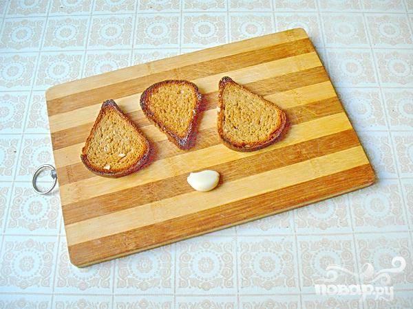 1. Первым делом надо приготовить сухарики. Нарежьте хлеб ломтиками и подсушите в духовке. Затем натрите сухарики чесноком.