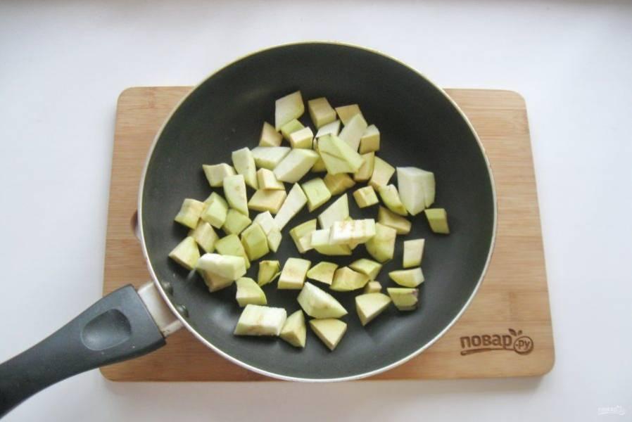 Баклажаны помойте, очистите и нарежьте кубиками. Выложите на горячую сковороду с растительным маслом.