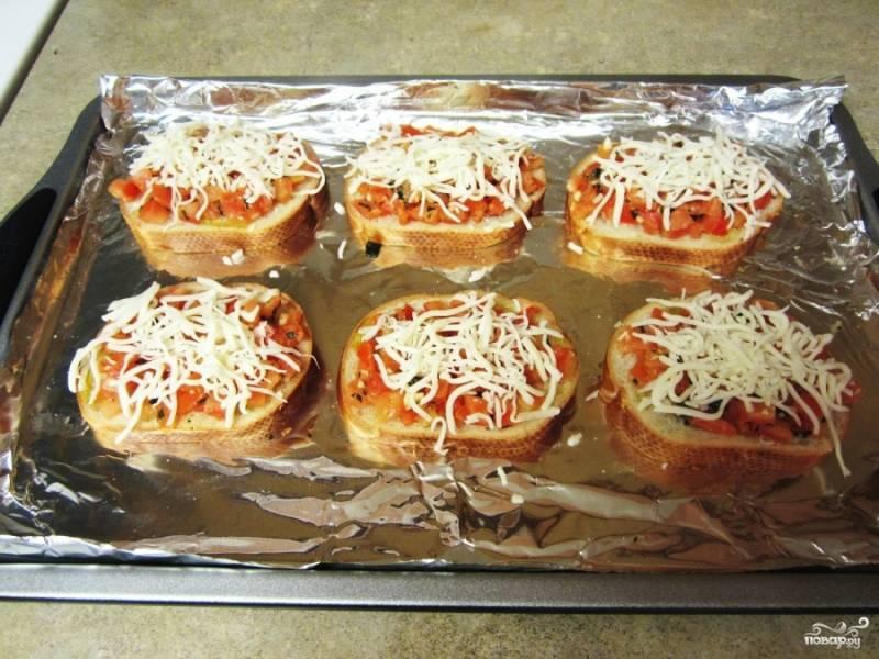 Натрите сыр моцарелла и посыпьте им бутерброды с помидорами.