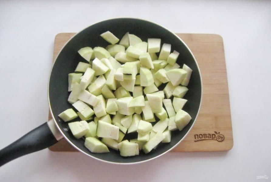 Баклажан помойте, очистите и нарежьте кубиками. Выложите в сковороду.