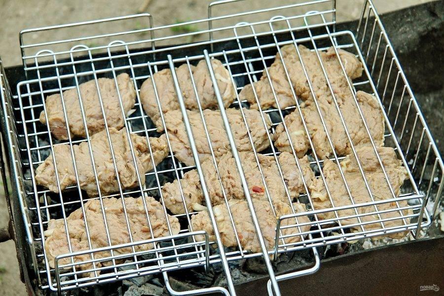 Подготовленные куски свинины выложите на смазанную маслом решетку.