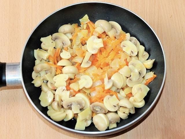 4. Теперь как следует разогреем сковородку. Добавим на неё немного подсолнечного масла. В нем пассеруем наш лучок (до размягчения). После перекладываем к луку морковь с грибочками, пассеруем и их (тоже пару минут). В конце добавляем измельченные зубчики чеснока. Подержим все вместе ещё пару минут — и снимаем с огня.