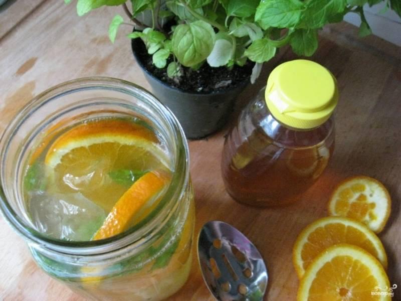 В банку со льдом добавьте апельсин (или мандарин, лайм, лимон), порезанный кольцами и промытые листья мяты.