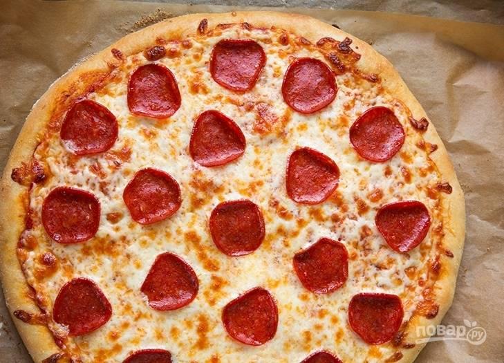 В заранее разогретую духовку отправьте пиццу запекаться на 15-20 минут, пока ее цвет не станет золотистым.