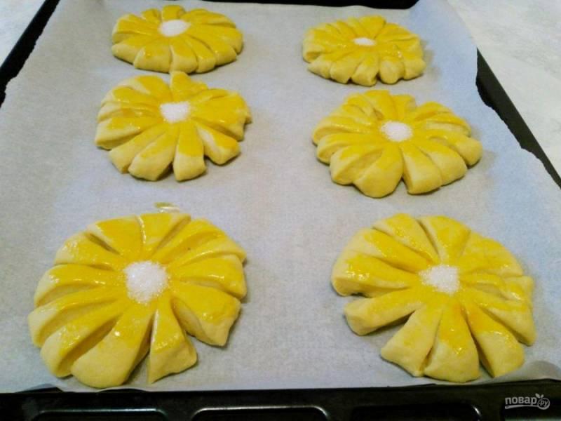 Разместите булочки на противне, застеленном пекарской бумагой, смажьте их поверхность оставленным ранее желтком и посыпьте центральную часть сахаром.