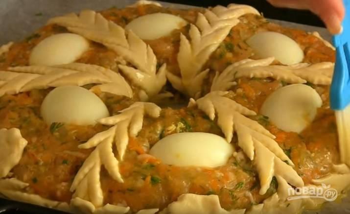 7. Три вареных яйца разрежьте вдоль на половинки или четверти и вдавите их в фарш. Извлеките стакан, выложите полоски из теста от центра к краю и по бокам, приклейте цветы. Смажьте желтком элементы из теста.