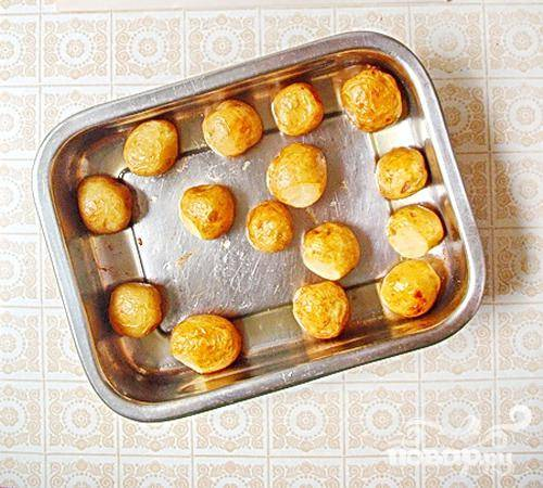 4.Приблизительно один час запекаем картофель на небольшом огне. При этом, несколько раз во время запекания мы его помешиваем, (для равномерного запекания со всех сторон). Проверяем готовность картофеля зубочисткой. После того, как картофель готов, перекладываем его на тарелку, чесноком натираем, немного поливаем маслом из противня, и посыпаем зеленью. Блюдо готово.