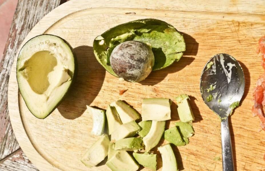 Вымойте авокадо, разрежьте его на две части. Удалите косточку и достаньте мякоть. Нарежьте ее на кусочки такого же размера, как и яблоки.