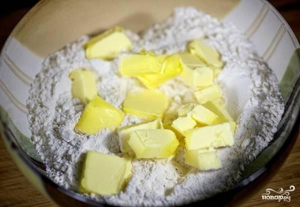 1. Для начала нужно приготовить тесто. Для этого в глубокую мисочку просейте муку и добавьте холодное сливочное масло, нарезанное небольшими кубиками.