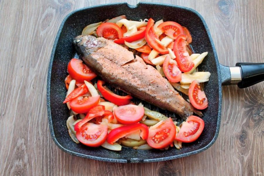 Помидор порежьте дольками и добавьте в сковороду к рыбе и овощам.