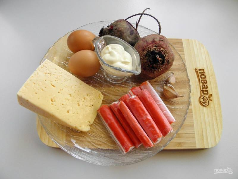 Подготовьте продукты для салата. Отварите или запеките в духовке свеклу. Остудите, снимите кожуру. Отварите яйца вкрутую, очистите. С крабовых палочек снимите обертки.