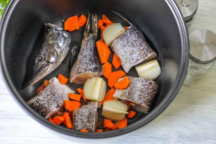 Щуку нарежьте крупными кусочками и выложите в чашу мультиварки. Очистите от кожуры лук и морковь, промойте в воде и разрежьте лук на четыре части, а морковь нарежьте крупными кусочками. Добавьте овощные нарезки в чашу к рыбе.