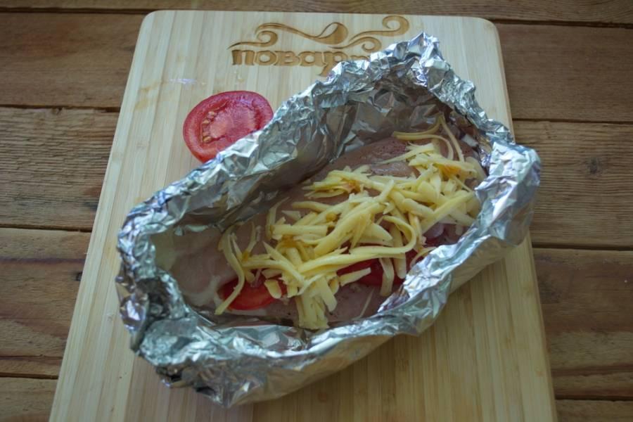 Из фольги сделайте поддончик. Уложите туда куриное филе. Верх филе смазать сметаной. Посыпать твердым тертым сыром. Разогрейте духовку до 200 градусов. Запекайте в открытом виде (не накрывая) около 20 минут.