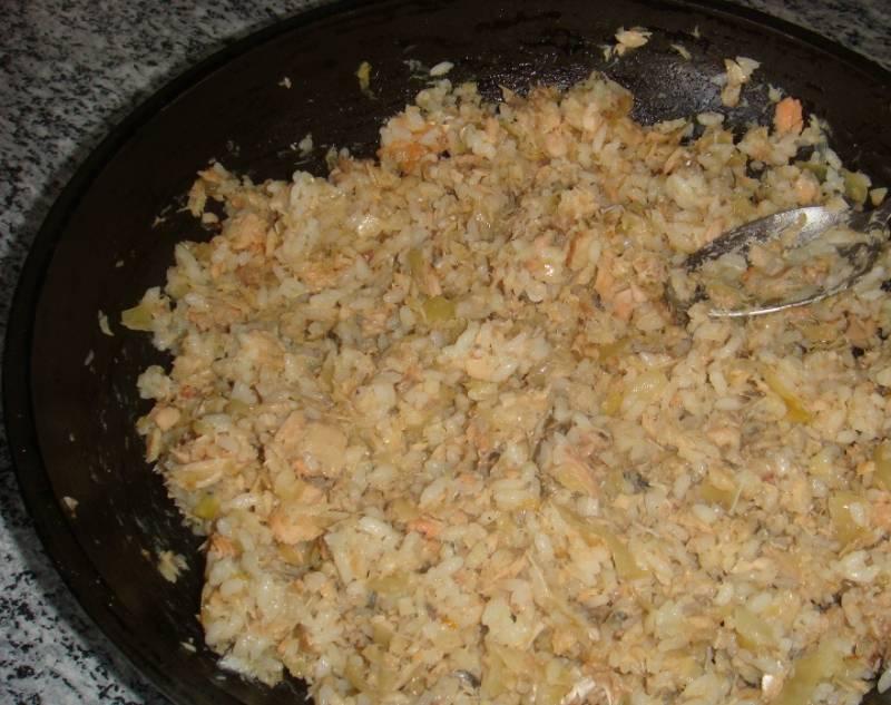 Приготовим начинку. Для этого обжариваем лук на сковороде, затем даем ему остыть и смешиваем с отваренным рыбным филе и сваренным рисом.