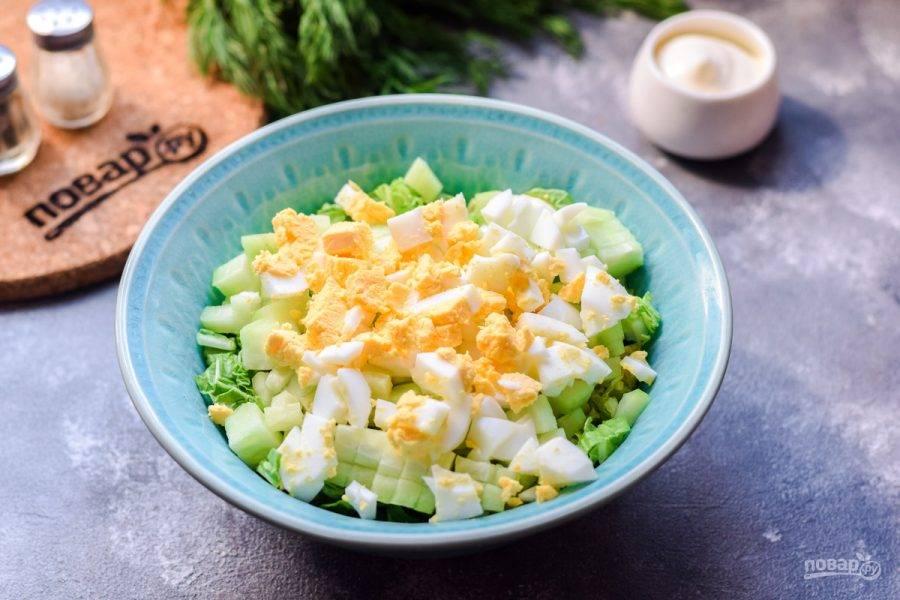 Вареное куриное яйцо почистите и нарежьте кубиками, добавьте следом в салат.