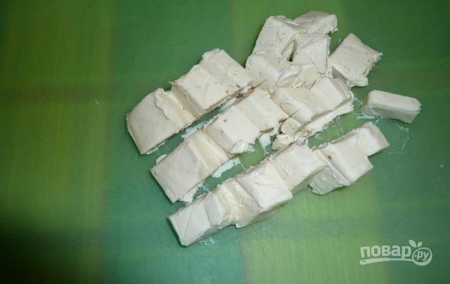 1.Можно использовать не только один сырок. Будет вкуснее, если использовать два или три. На 10 минут помещаю плавленый сыр в морозильную камеру, затем освобождаю от упаковки и нарезаю небольшими кубиками.