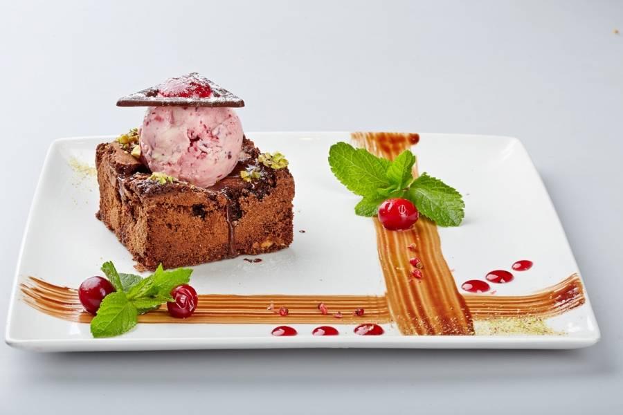5. Охладить. Разрезать на квадраты. Украсить шоколадным ганашем, шариком клюквенного мороженого и веточкой мяты.