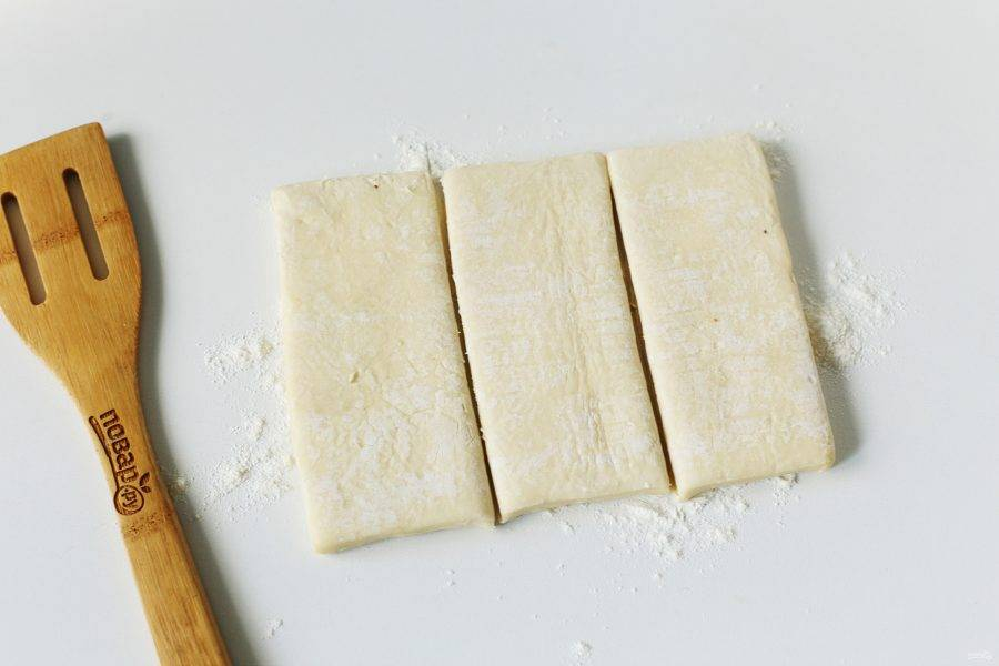 Рабочую поверхность посыпьте мукой, выложите размороженный пласт теста и разрежьте его вдоль на три части как на фото.