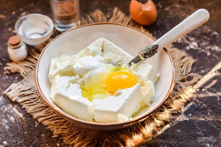 Добавьте к творогу яйцо и порцию сметаны.