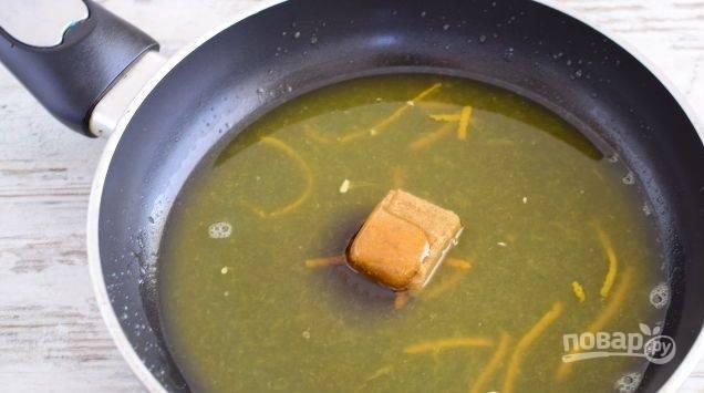 Теперь займитесь соусом. Из апельсина выжмите сок на сковороду и добавьте цедру. Внесите мёд, бульонный кубик и соевый соус. Прогревайте смесь несколько минут. Затем добавьте крахмал. Перемешайте соус и немного его потушите до густоты.