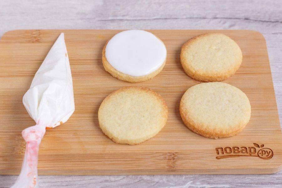 Отрежьте кончик кондитерского мешка и покройте глазурью полностью остывшее печенье.