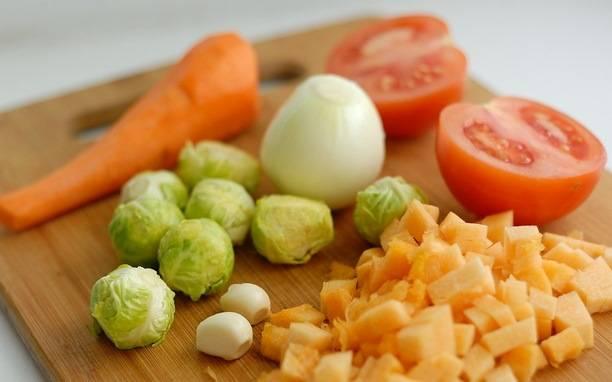 Овощи промойте и очистите. Морковь нашинкуйте, как для жюльена, капусту порежьте четвертинками, лук, тыкву и помидоры кубиками.