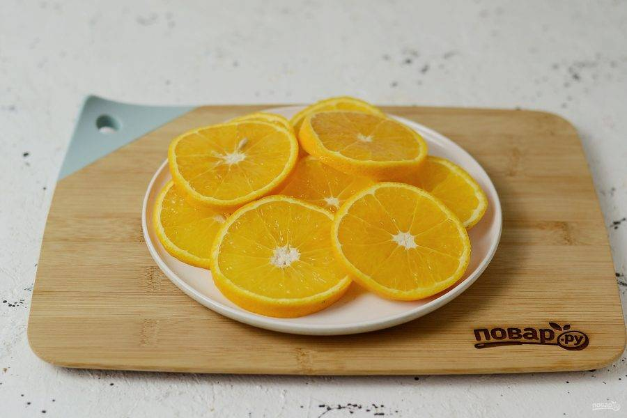Апельсины помойте, обсушите. Нарежьте кружочками толщиной полсантиметра. Отварите апельсины в кипящей воде примерно 4-5 минут, затем откиньте на сито, чтобы стекла лишняя жидкость. Это уберет лишнюю горечь из кожуры.
