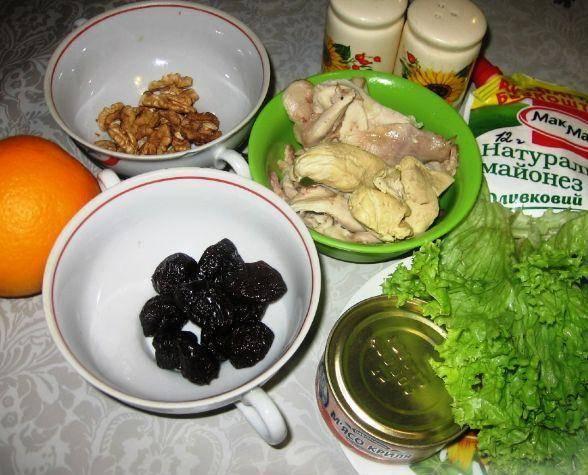 1. Подготовим ингредиенты. Апельсин очищаем от кожуры, семечек и белых волокон. Чернослив заливаем кипятком, а когда распарится, измельчим. Курицу режем кубиками.