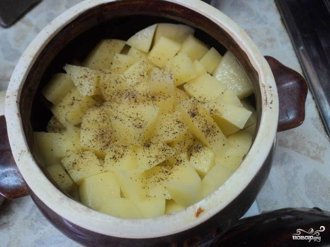 Горшочек смазываем небольшим количеством растительного масла и выкладываем в него сначала лук, затем мясо и картофель. Сверху посыпаем солью и черным молотым перцем, а при желании можете добавить и другие специи.