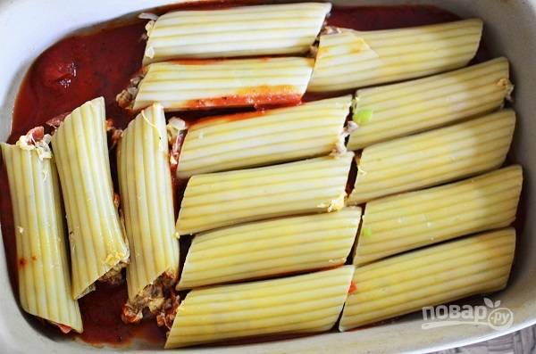 3. Выложите половину томатного соуса на дно жаропрочной формы, распределите ровным слоем. Сверху — маникотти.